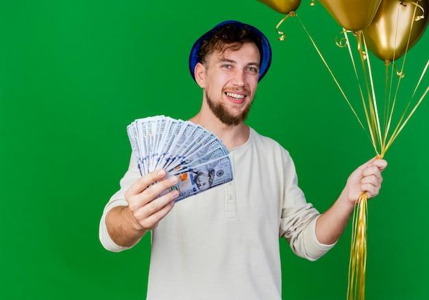 Радостный молодой красивый славянский тусовщик в партийной шляпе держит воздушные шары и протягивает деньги и смотрит в камеру, изолированную на зеленом фоне с копией пространства
