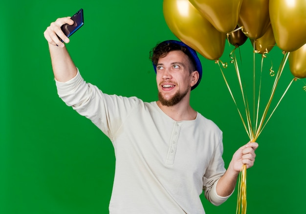 Радостный молодой красивый славянский тусовщик в партийной шляпе, держащий воздушные шары, делающий селфи на зеленом фоне