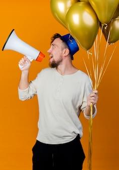 オレンジ色の背景に分離されたスピーカーで話している風船を持って頭を左右に回すパーティーハットを身に着けているうれしそうな若いハンサムなスラブ党の男