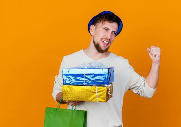 종이 가방과 선물 상자를 들고 파티 모자를 쓰고 즐거운 젊은 잘 생긴 슬라브 파티 남자가 복사 공간이 오렌지 배경에 고립 된 예 제스처를하고있는 쪽을보고