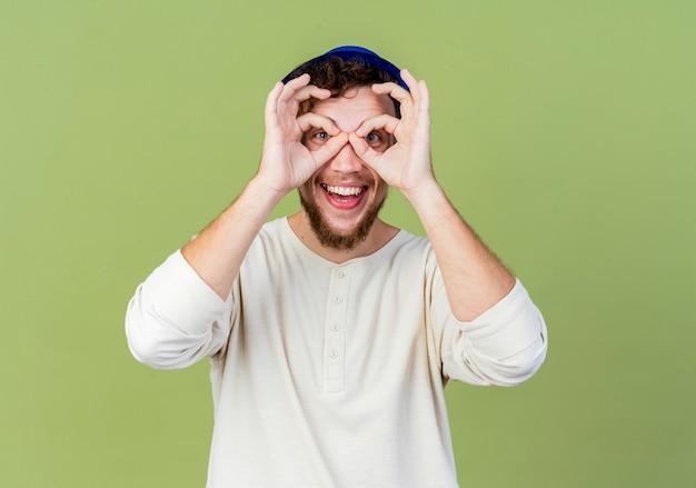 Радостный молодой красивый славянский тусовщик в партийной шляпе, смотрящий в камеру, делает жест взгляда, используя руки как бинокль, изолированные на оливково-зеленом фоне с копией пространства