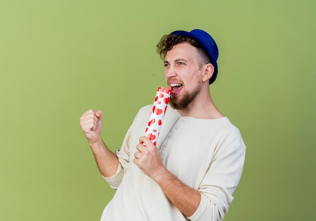 Joyful young handsome slavic party guy wearing party hat looking straight singing using confetti cannon as microphone isolated on olive green background with copy space