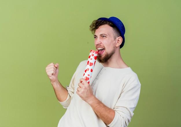 コピースペースでオリーブグリーンの背景に分離されたマイクとして紙吹雪の大砲を使用してまっすぐに歌うパーティーハットを身に着けているうれしそうな若いハンサムなスラブパーティー男