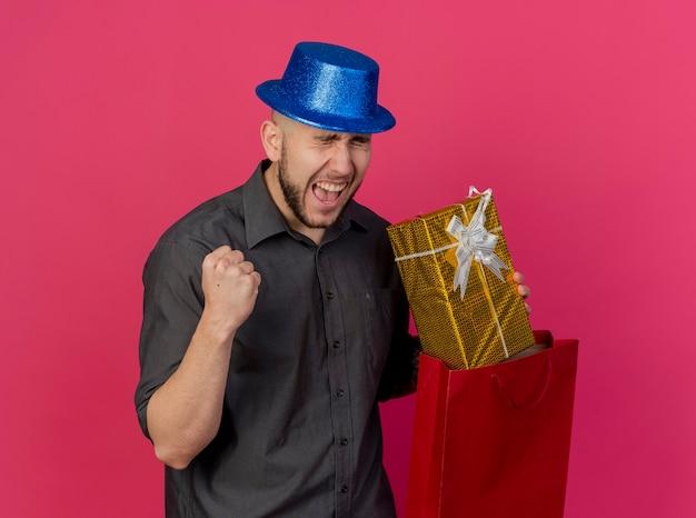 パーティーハットを身に着けているうれしそうな若いハンサムなスラブパーティーの男は、真っ赤な背景に分離されたはいジェスチャーを行う紙袋からギフトパックを引き出します