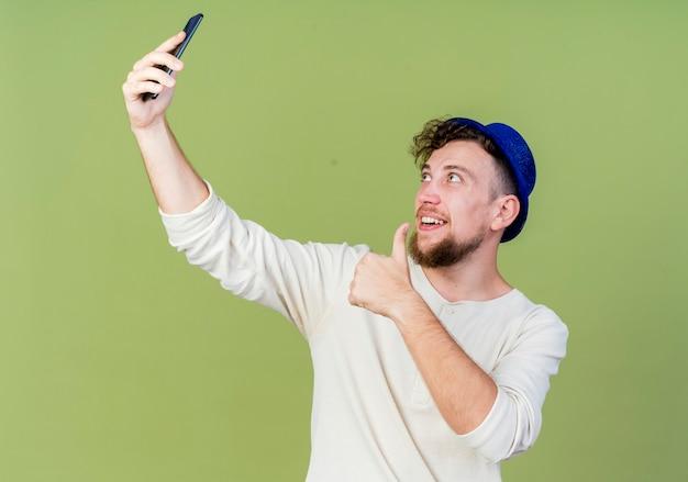 うれしそうな若いハンサムなスラブパーティーの男は、オリーブグリーンの背景で隔離のselfieを取る親指を示すパーティー帽子をかぶっています