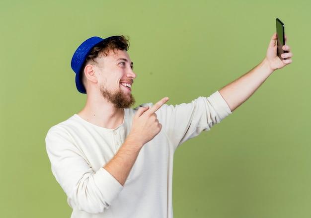 オリーブグリーンの背景で隔離の携帯電話を指してselfieを取るパーティー帽子をかぶってうれしそうな若いハンサムなスラブパーティー男