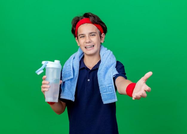 ヘッドバンドとリストバンドを身に着けているうれしそうな若いハンサムなスポーティな少年は、緑の背景に分離されたカメラを見て、手を伸ばして水筒を持って首の周りに歯列矯正器とタオルを持っています