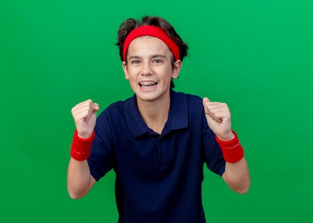 緑の背景に分離されたはいジェスチャーを行うカメラを見て歯科用ブレースとヘッドバンドとリストバンドを身に着けているうれしそうな若いハンサムなスポーティな少年