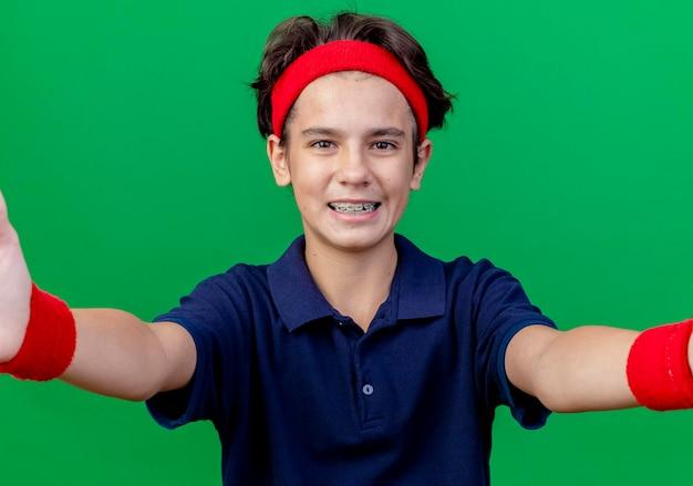 치과 교정기와 머리띠와 팔찌를 입고 즐거운 젊은 잘 생긴 스포티 한 소년이 앞을보고 녹색 벽에 고립 된 앞쪽으로 손을 뻗어