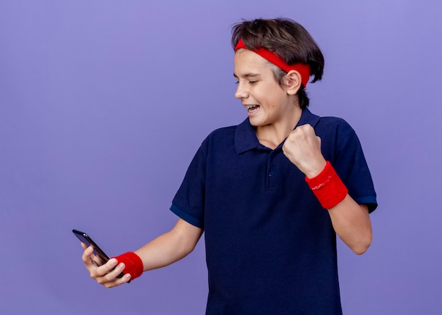 Gioioso giovane ragazzo sportivo bello che indossa la fascia e braccialetti con le parentesi graffe dentali che tengono il telefono cellulare che fa il gesto di sì isolato sulla parete viola