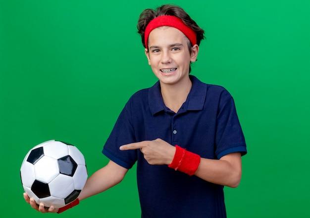 Gioioso giovane ragazzo sportivo bello che indossa fascia e braccialetti con bretelle dentali guardando la tenuta anteriore e indicando il pallone da calcio isolato sulla parete verde con lo spazio della copia