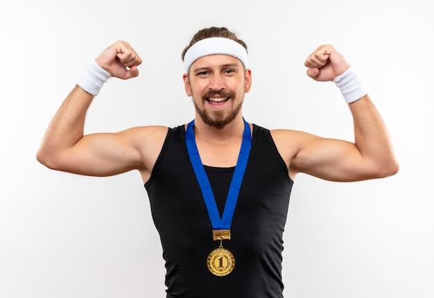 목에 머리띠와 팔찌와 메달을 입고 즐거운 젊은 잘 생긴 스포티 한 남자가 강한 흰 벽에 고립 된 몸짓