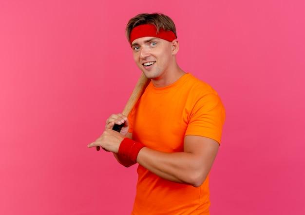 핑크에 고립 된 어깨에 야구 방망이를 들고 머리띠와 팔찌를 입고 즐거운 젊은 잘 생긴 스포티 한 남자