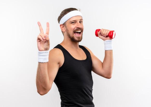 Радостный молодой красивый спортивный мужчина с повязкой на голову и браслетами держит гантель и делает знак мира на белой стене