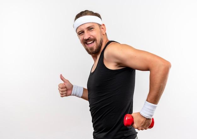 Радостный молодой красивый спортивный мужчина с головной повязкой и браслетами держит гантель и показывает большой палец вверх, стоя в профиль, изолированном на белой стене с копией пространства