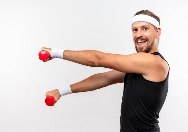 Радостный молодой красивый спортивный мужчина с головной повязкой и браслетами держит гантели и протягивает руки, стоя в профиль, изолированном на белой стене