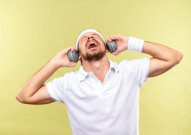 Gioioso giovane bell'uomo sportivo che indossa fascia e braccialetti e cuffie che si gode la musica con gli occhi chiusi e con le mani sulle cuffie isolate sul muro verde