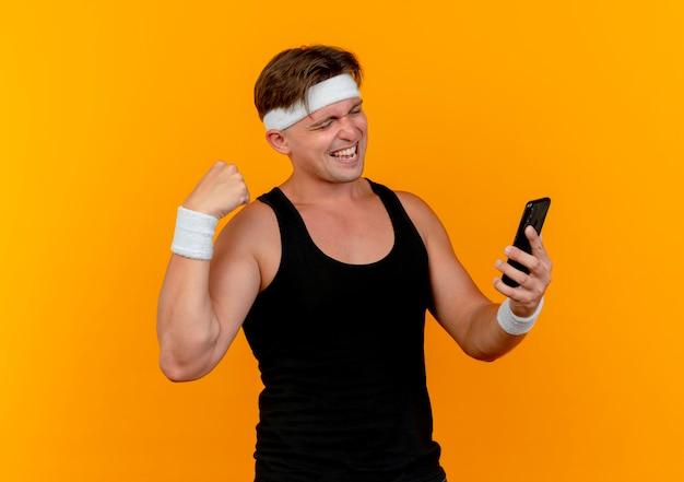 Gioioso giovane bell'uomo sportivo che indossa la fascia e braccialetti che tengono e guardando il telefono cellulare e gesticolando forte isolato sull'arancio