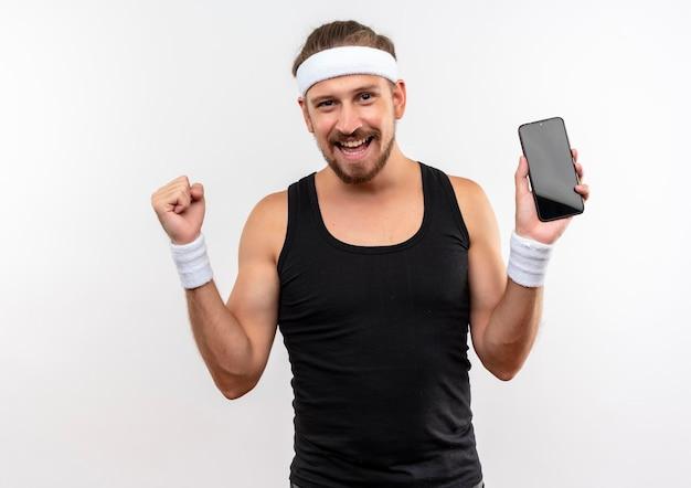 Gioioso giovane bello sportivo che indossa fascia e braccialetti che tengono il telefono cellulare e il pugno serrato isolato su muro bianco white