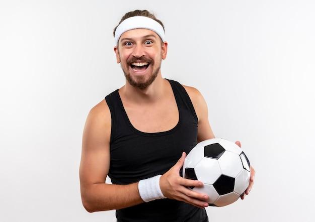 Gioioso giovane bello sportivo che indossa fascia e braccialetti che tengono un pallone da calcio che sembra isolato su un muro bianco