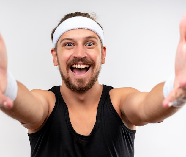 Joyful young handsome sporty man wearing headband and wristbands stretching out hands  isolated on white wall