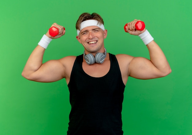 Joyful young handsome sporty man wearing headband and wristbands with headphones on neck raising dumbbells isolated on green