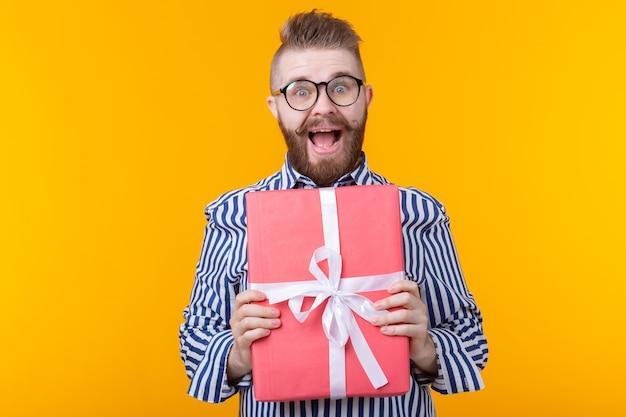 Радостный молодой хипстерский парень с усами в очках обнимает красную подарочную коробку