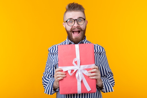 Joyful young hipster guy with a mustache in glasses hugs a red gift box