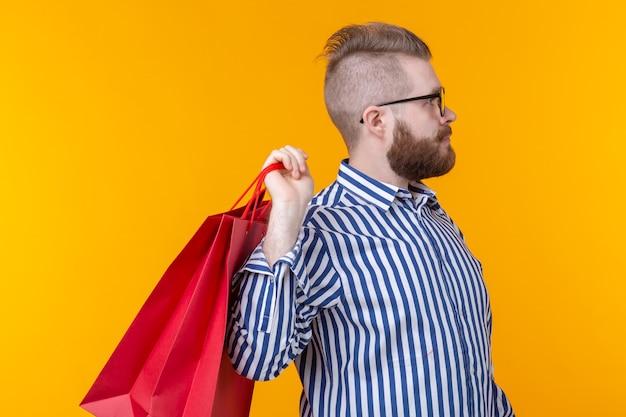 즐거운 젊은 hipster 빨간 쇼핑백을 들고있다