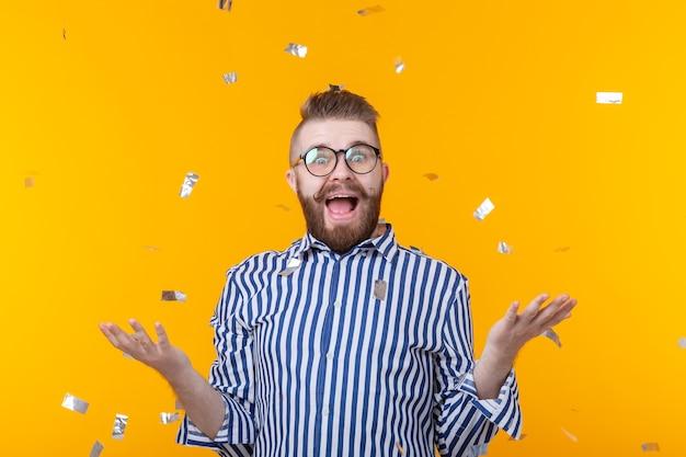 眼鏡をかけたうれしそうな若いヒップスターの男性は、黄色の壁に飛んでいる紙吹雪の中で幸せに笑っています