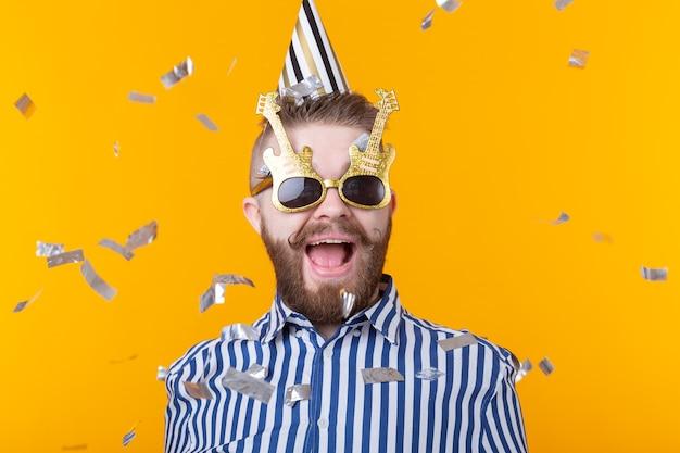 종이 모자와 안경에 즐거운 젊은 힙 스터 남성은에 색종이 비행 중 행복 하 게 웃 고있다