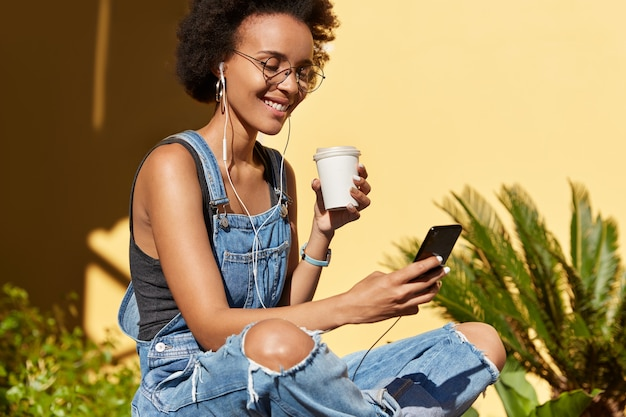 Joyful young hipster with curly bushy hair, wears spectacles and ragged overalls, downloads song to mobile phone playlist, drinks fresh drink from disposable cup, enjoys spare time during summer