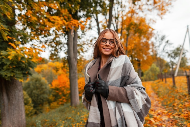 Joyful young hipster woman in a fashionable knitted scarf in stylish glasses in a trendy coat posing in a park outside the city. cheerful girl model with a positive smile walks in the forest. autumn.