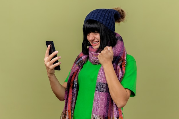 Gioiosa giovane ragazza caucasica malata che indossa cappello invernale e sciarpa che tiene guardando il telefono cellulare tenendo il tovagliolo facendo sì gesto isolato su sfondo verde oliva con lo spazio della copia