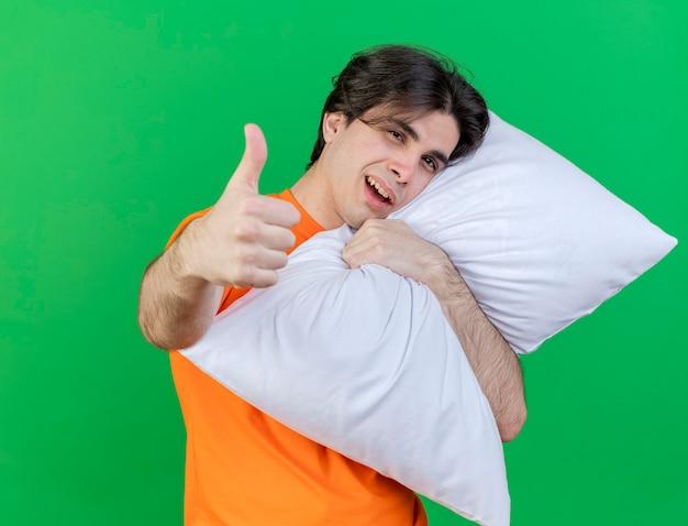 うれしそうな若い病気の人は枕を抱きしめ、緑の背景で隔離の親指を表示