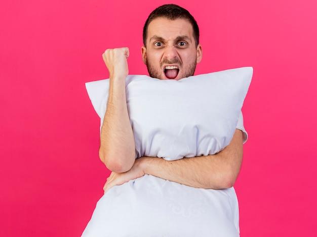 Gioioso giovane uomo malato abbracciò il cuscino che mostra sì gesto isolato su sfondo rosa