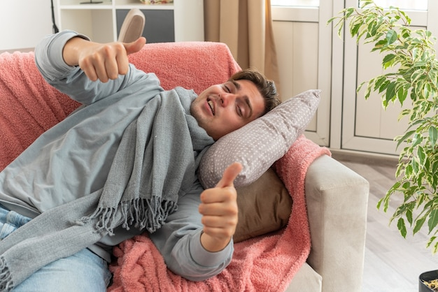 목에 스카프를 두른 즐거운 젊은 아픈 남자가 거실에서 소파에 누워 엄지손가락을 치켜들고 있다