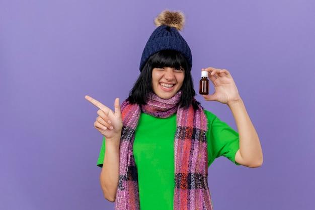 冬の帽子とスカーフを身に着けているうれしそうな若い病気の女性は、コピースペースで紫色の壁に隔離された側を指しているガラスの薬剤を保持している正面を見て