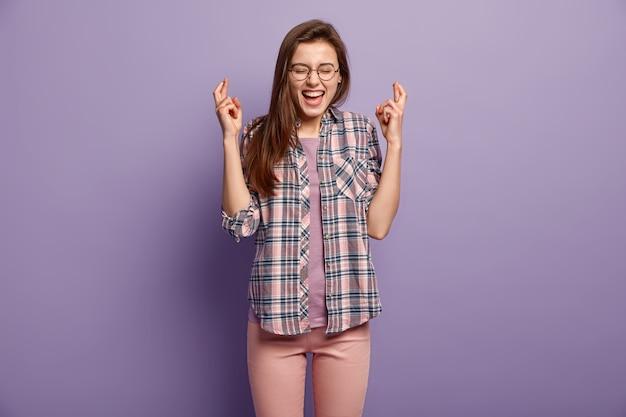 즐거운 젊은 아가씨는 손가락을 교차시키고, 원하는 것을 기다립니다. 둥근 안경을 착용합니다.