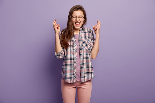 Joyful young lady keeps fingers crossed, waits for something desirable, wears round spectacles