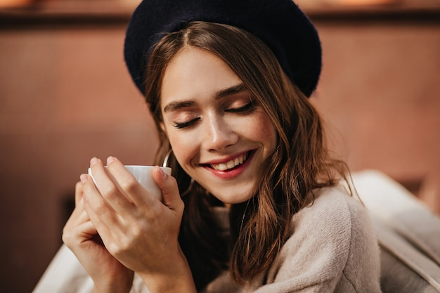 붉은 입술, 닫힌 눈, 갈색 머리, 세련된 베레모, 베이지색 풀오버를 입은 즐거운 젊은 여성이 야외에 앉아 웃고 화창한 가을날 흰색 차 한 잔을 들고 있습니다.