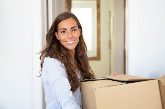 Joyful young latin woman moving into new apartment, holding and carrying carton box,