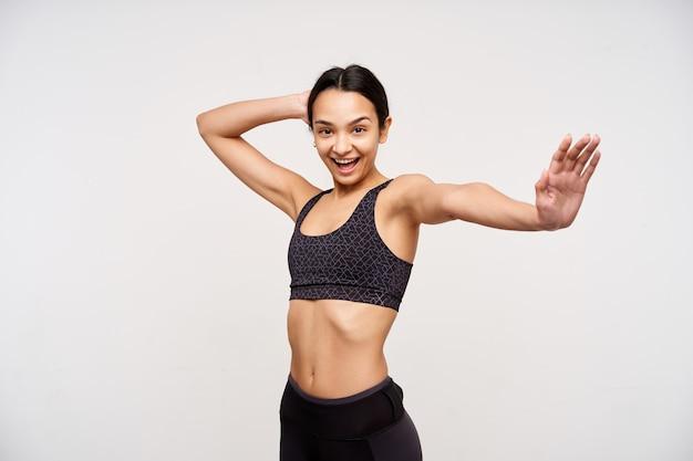 흰 벽 위에 서있는 그녀의 팔을 훈련하는 동안 행복하게 앞에서 찾고 즐거운 젊은 사랑스러운 갈색 눈 갈색 머리 여자. 스포츠와 건강한 라이프 스타일 컨셉