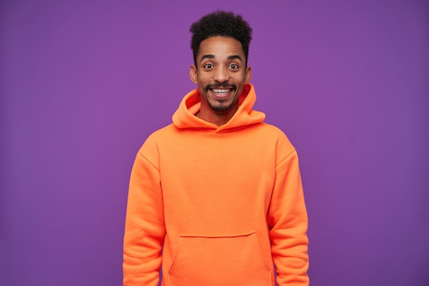 Joyful young lovely brown-eyed dark skinned brunette male with beard looking surprisedly and smiling widely while standing on purple in sporty wear