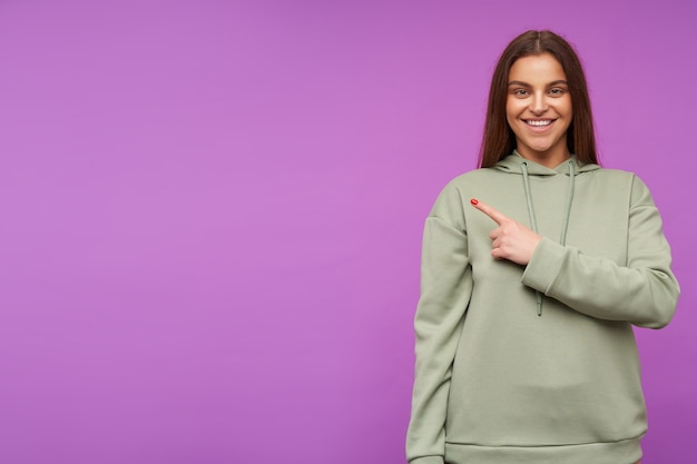 Joyful young lovely brown haired woman dressed in mint hoodie smiling broadly while showing aside with index finger, standing against purple wall