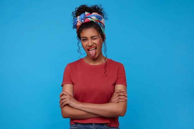 彼女の舌を突き出している間、交差した手で青い壁の上にポーズをとっている間、お祝いの化粧をしているうれしそうな若い素敵なブルネットの巻き毛の女性