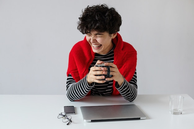 短いトレンディなヘアカットとうれしそうな若い素敵な巻き毛のブルネットの女性は、白い背景に座って、仕事の日にコーヒーブレイクをしながら目を閉じて幸せに笑っています