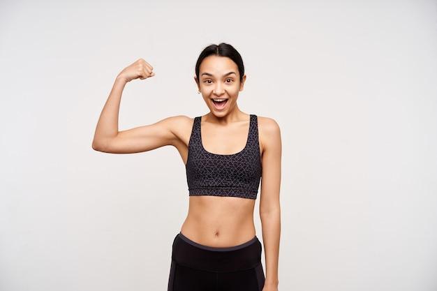 Радостная молодая милая темноволосая женщина, одетая в спортивную одежду, держит руку поднятой, взволнованно глядя вперед с широко открытым ртом, изолированная на белой стене