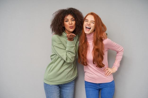 灰色の壁に隔離された空気のキスを吹く巻き毛の暗い肌のブルネットの女性を抱きしめながら幸せにウインクするカジュアルな髪型のうれしそうな若い素敵な赤毛の女性