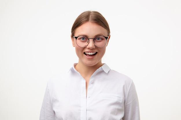 Gioiosa giovane adorabile femmina con testa bianca con acconciatura casual che ride felicemente mentre guarda allegramente in telecamera, isolate su sfondo bianco con le mani verso il basso